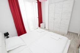 Спальня. Черногория, Сутоморе : Современный апартамент возле пляжа, с большим балконом и шикарным видом на море, с гостиной и двумя отдельными спальнями.