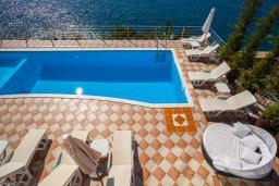 Зона отдыха у бассейна. Черногория, Добра Вода : 3-х этажный дом в Добра Вода, площадью 450м2 с 7-ю спальнями, с 4-ю ванными комнатами, с 2-мя большими гостиными, с большим бассейном, с террас открывается шикарный вид на море, с местом для барбекю